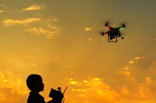 04 Jan 2015 --- Silhouette of boy playing quadcopter during sunset --- Image by © nasrul_effendy/RooM the Agency/Corbis