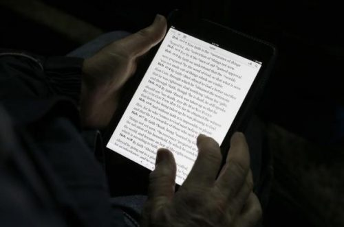 "A man reads the bible from an iPad mini at the ""Christ is the Answer International Ministries"" group's camp near Florence February 2, 2013.  REUTERS/Max Rossi"